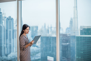 Businesswoman using digital tablet at window, Dubai, United Arab Emiratesの写真素材 [FYI03544931]