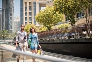 Couple strolling on walkway carrying shopping bags, Dubai, United Arab Emiratesの写真素材 [FYI03545015]