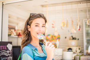 Portrait of woman with lollipop from sweet stall, Dubai, United Arab Emiratesの写真素材 [FYI03545019]