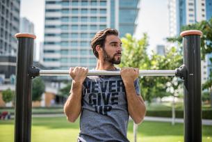 Young man doing pull ups on park exercise equipment, Dubai, United Arab Emiratesの写真素材 [FYI03545037]