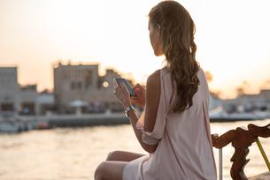 Woman reading smartphone texts on boat at Dubai marina, United Arab Emiratesの写真素材 [FYI03545065]