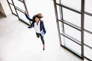 High angle view of businesswoman running through office entranceの写真素材 [FYI03545114]