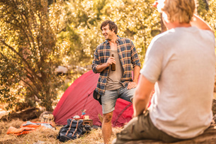 Male campers chatting  and drinking beer in forest, Deer Park, Cape Town, South Africaの写真素材 [FYI03545224]