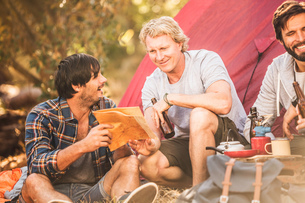 Three men reading map whilst camping in forest, Deer Park, Cape Town, South Africaの写真素材 [FYI03545230]
