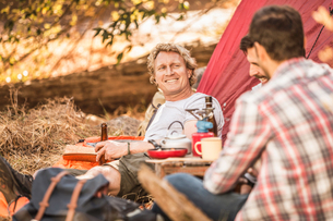 Men camping in forest drinking beer and coffee, Deer Park, Cape Town, South Africaの写真素材 [FYI03545234]
