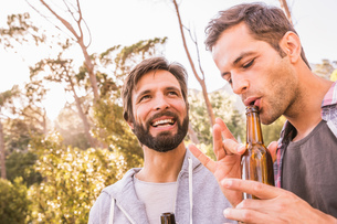 Two men blowing into beer bottle whilst camping in forest, Deer Park, Cape Town, South Africaの写真素材 [FYI03545289]