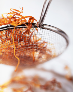 Deep fried carrot in sieve, close-upの写真素材 [FYI03545323]