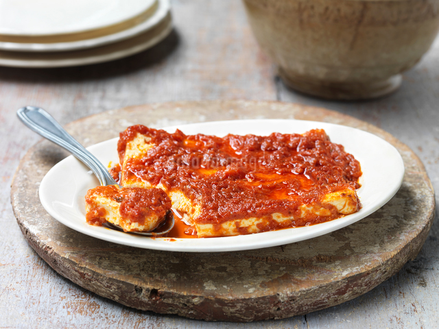 Baked feta cheese with sun dried tomato sauce, in bowl with spoonの写真素材 [FYI03545333]