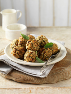Sage and onion stuffing balls, with green herbs on plateの写真素材 [FYI03545386]