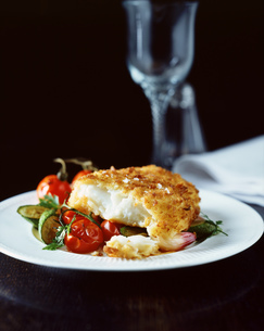 Breaded fish with mediterranean vegetables on white plateの写真素材 [FYI03545410]