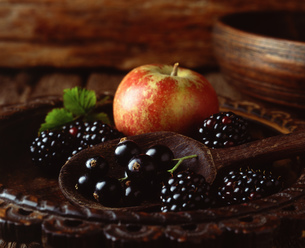 Apple, blackberries and blackcurrants in vintage wooden bowl with wooden spoon, close-upの写真素材 [FYI03545419]