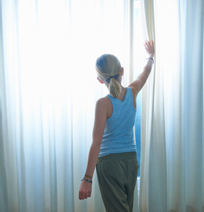 Rear view of girl peering through net curtained windowの写真素材 [FYI03545483]