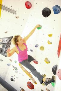 Woman climbing indoor artificial climbing wallの写真素材 [FYI03545513]