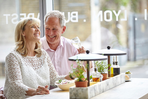 Mature dating couple laughing at restaurant lunch, London, UKの写真素材 [FYI03545551]