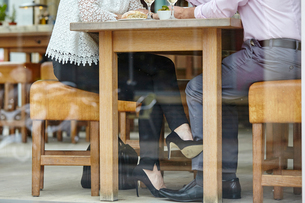 Waist down view of womans high heel shoe touching mans leg at restaurant tableの写真素材 [FYI03545553]