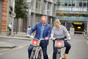 Mature dating couple laughing whilst cycling on hire bicycles, London, UKの写真素材 [FYI03545560]