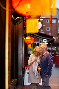 Mature couple reading restaurant menu in China Town at dusk, London, UKの写真素材 [FYI03545572]