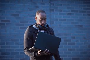 Man with headphones holding laptopの写真素材 [FYI03545580]
