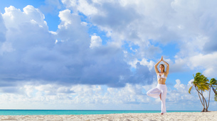 Young woman practising yoga tree pose on beach, Dominican Republic, The Caribbeanの写真素材 [FYI03545674]