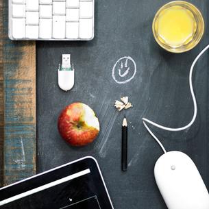 Overhead view computer equipment, apple and orange juice on blackboard surfaceの写真素材 [FYI03545708]
