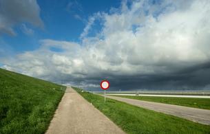 Clouds above pathway and commercial greenhouse, 'S Gravenpolder, Zeeland, Netherlandsの写真素材 [FYI03545751]