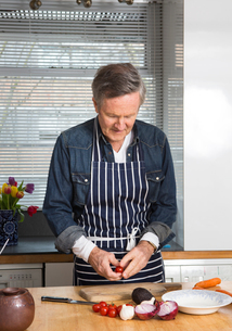 Man preparing food in kitchenの写真素材 [FYI03545780]