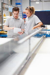 Manager and female worker looking at digital tablet on production line in factoryの写真素材 [FYI03545929]