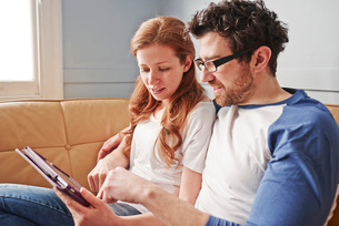 Mid adult couple relaxing on sofa looking at digital tabletの写真素材 [FYI03545973]