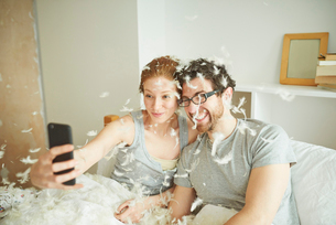Mid adult couple covered in pillow fight feathers taking smartphone selfie in bedの写真素材 [FYI03546010]