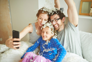 Mid adult couple and daughter covered in pillow fight feathers taking smartphone selfie in bedの写真素材 [FYI03546016]