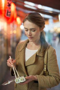 Woman eating takeaway sushi on city street at nightの写真素材 [FYI03546026]