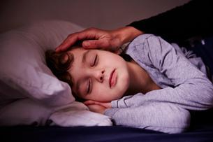 Mothers hand stroking sleeping boyの写真素材 [FYI03546118]