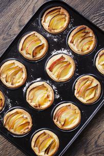 Overhead view of miniature frangipane apple tarts in baking trayの写真素材 [FYI03546323]
