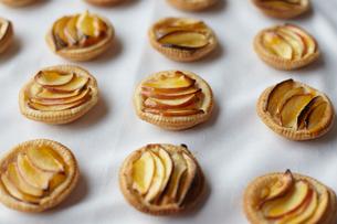 Miniature frangipane apple tarts on tableclothの写真素材 [FYI03546326]