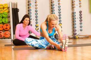 Women in gym sitting on yoga mat doing leg stretching exercisesの写真素材 [FYI03546423]