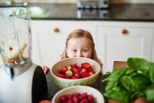 Girl peeking over bowls of strawberries of kitchen counterの写真素材 [FYI03546468]
