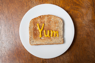 Overhead view of the word yum written on ham on toast in mustardの写真素材 [FYI03546713]