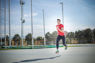 Young male sprinter sprinting at sport facilityの写真素材 [FYI03546737]