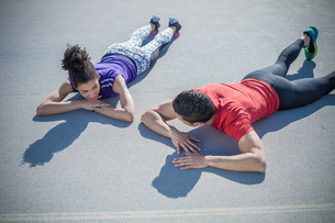 Overhead view of young man and woman training, taking a break on asphaltの写真素材 [FYI03546746]