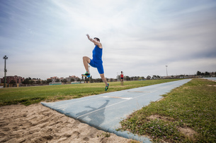 Young male long jumper jumping mid air at sport facilityの写真素材 [FYI03546753]