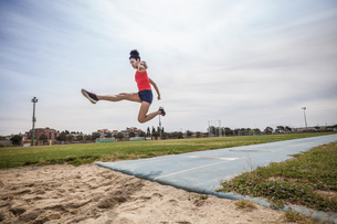 Young female long jumper jumping mid air at sport facilityの写真素材 [FYI03546754]