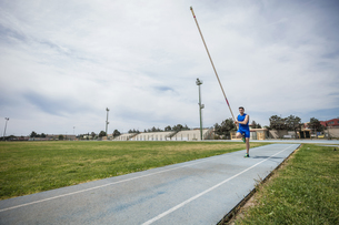 Young male pole vaulter sprinting with pole vault at sport facilityの写真素材 [FYI03546756]