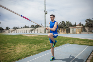 Young male pole vaulter pole vaulting at sport facilityの写真素材 [FYI03546757]