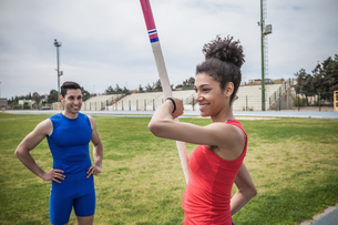Instructor advising young female pole vaulter at sport facilityの写真素材 [FYI03546759]