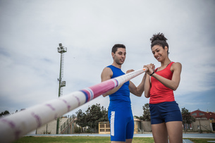 Man instructing young female pole vaulter at sport facilityの写真素材 [FYI03546760]