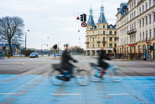 Two cyclists speeding along blue city cycle path, Copenhagen, Denmarkの写真素材 [FYI03546817]