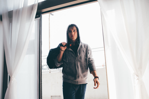 Man in doorway wearing hooded top carrying holdall on shoulderの写真素材 [FYI03546824]