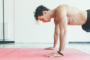 Side view of man in gym doing push upsの写真素材 [FYI03546838]