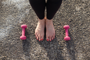 Mature woman standing barefoot, hand weights on floor beside her, elevated view, focus con feetの写真素材 [FYI03546965]