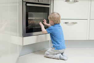 Young boy sitting in front of oven, looking through glass, rear viewの写真素材 [FYI03547086]